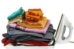 Clothes stacked next to an iron stock images