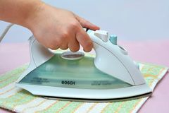 Ironing clean linen with hot Bosch iron Stock Photos