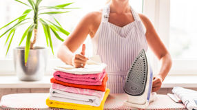Ironing clothes on ironing board, ironed clothes ironing, laundry, clothes, housekeeping and objects concept - close up of ironed royalty free stock photo