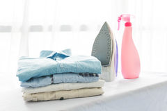 Ironing, clothes, housework and objects concept. Close up of iron and clothes on table at home Stock Image