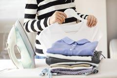 Ironing clothes on ironing board Stock Photo