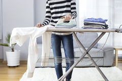 Ironing clothes on ironing board Royalty Free Stock Images