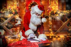 Ironing clothes santa. Portrait of Santa Claus ironing cloth. Christmas and New Year concept royalty free stock photography