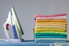 Ironing colorful towels. Housework, ironing iron colorful towels on the ironing board Stock Photos