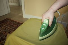 Ironing with iron and hand stock images
