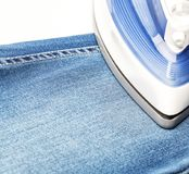 Ironing blue jeans on a white baclground Stock Image