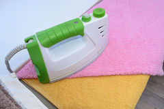 Ironing linen with iron. A stack of ironed towels lying next to the iron. Hot iron on an Ironing Board. Teflon sole plate covered Stock Photography