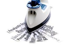 Ironing out the economy. Iron on economic news headlines to indicate ironing out the economy royalty free stock images