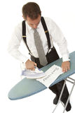 Ironing out problems 1. Metaphor - a businessman ironing out problems Stock Image