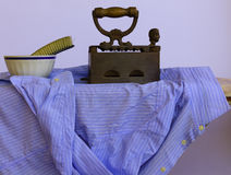 Ironing a shirt. Moisten the laundry with a brush before ironing the striped shirt with the old cast iron Stock Image