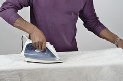 Ironing a tablecloth. Man ironing a white tablecloth with an electric iron Royalty Free Stock Images