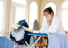 Ironing too many shirts. A frustrated woman looking at a pile of shirts needing to be ironed with an expression of exasperation Royalty Free Stock Image