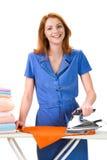 Ironing towels. Portrait of joyful female ironing towels over white background Royalty Free Stock Photos