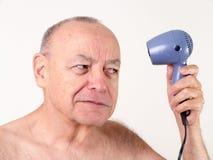 Ironisch - kahler Mann, der Haartrockner verwendet Lizenzfreie Stockfotos