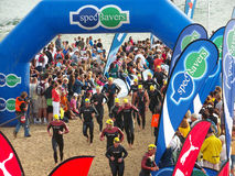 Ironman SA 2008. Competitors in the Ironman SA 2008 triathlon run under a arch after finishing a lap of swimming Royalty Free Stock Images