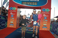 Ironman south africa. Mauritz janse van rensburg crosses the line during the ironman south african triangle event.with him is his son and daughter.the event took Royalty Free Stock Image