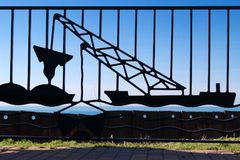 Ironwork Detail of Lake Dredger. A nautical vesslle called a  dredger, engineered for underwater excavation is the detail on this fence railing at Cleveland`s Stock Photo