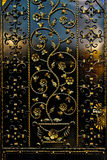 Ironwork fence. Ironwork black fence with golden floral decor stock photo