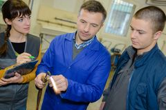 Ironworks teacher showing students how to securely use gas welder stock photos