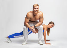 Irony - male brutal trainer sit on woman doing push ups Stock Image