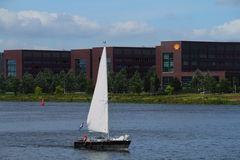 Irony - wind energy and oil company. A yacht sails past an oil company building using wind energy in Amsterdam Harbor the Netherlands Stock Photo