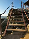 The irony wooden ladder with bended steel handrail in touristic path to viewpoint. Wooden worn out steps covered by light sand Royalty Free Stock Photos