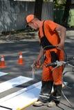 IRPIN, УКРАИНА - 6-ОЕ МАЯ 2017: Работник красит пешеходный crosswalk Технические картина работника человека дороги и pedestr заме Стоковые Фото