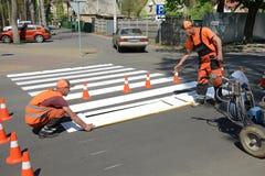 IRPIN UKRAINA - MAJ 06, 2017: Arbetare som målar en fot- övergångsställe Maskin för målarfärg för vägmarkering Arkivfoto