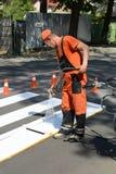 IRPIN UKRAINA, MAJ, - 06, 2017: Pracownik maluje zwyczajnego crosswalk r Fotografia Royalty Free