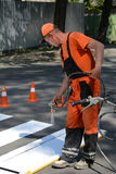 IRPIN, UKRAINE - MAY 06, 2017: Worker is painting a pedestrian crosswalk. Technical road man worker painting and remarking pedestr. UKRAINE - MAY 06, 2017 Stock Photos
