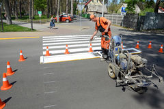 IRPIN, UKRAINE - MAY 06, 2017: Worker is painting a pedestrian crosswalk. Technical road man worker painting and remarking pedestr. UKRAINE - MAY 06, 2017 Stock Images