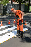 IRPIN, UKRAINE - MAY 06, 2017: Worker is painting a pedestrian crosswalk. Technical road man worker painting and remarking pedestr. UKRAINE - MAY 06, 2017 Royalty Free Stock Photography