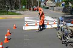 IRPIN, UKRAINE - MAY 06, 2017: Worker is painting a pedestrian crosswalk. Technical road man worker painting and remarking pedestr. UKRAINE - MAY 06, 2017 Stock Photo