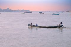 IRRAWADY RIVER, MYANMAR - Boats on the Irrawady river in Myanmar at sunset. IRRAWADY RIVER, MYANMAR - November 17, 2015: Boats on the Irrawaddy River at sunrise Royalty Free Stock Images