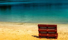 Irrealny obrazek końcówka lato przy jeziorem z pustą plażą i pokładu krzesłem robić europallets zdjęcia stock