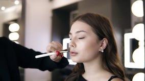 Irreconocible componga al artista que aplica la fundación dura en la cara de la mujer joven Maquillaje profesional en sal?n Cierr almacen de metraje de vídeo