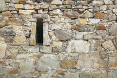 Irregular fieldstone wall with an arrow slit.  Stock Photos
