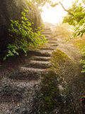 Irregular natural steps carved in the granite rock. Way to the summit illuminated by the sun royalty free stock photography