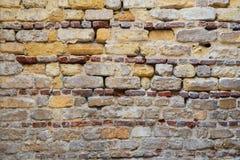 Irregular pattern of yellowish, red and gray grunge weathered uneven bricks stone wall surface. Background of irregular pattern of yellowish, red and gray grunge Stock Image