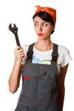 Irresolute girl with spanner Royalty Free Stock Photos