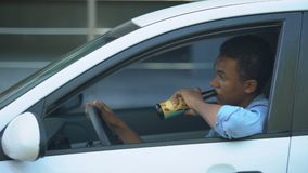 Irresponsible african-american teenager drinking beer driving car, accident risk. Stock footage stock video footage