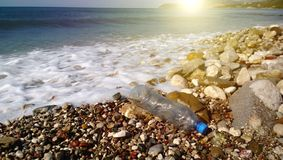 The irresponsible attitude of humanity towards nature: a beached empty plastic bottle on the background of beautiful nature. Sea, sun, mountains royalty free stock photo