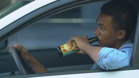 Irresponsible black teen boy drinking beer on driver place, risk of accident. Stock footage stock footage
