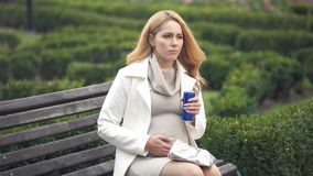 Irresponsible expectant drinking unhealthy soft drink on bench, baby health care. Stock photo stock photos