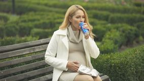 Irresponsible expectant drinking unhealthy soft drink on bench, baby health care. Stock footage stock video footage