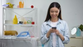 Irresponsible housewife chatting on smartphone, leaving hot iron on board. Stock footage stock video