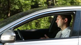 Irresponsible man throwing trash out of car window stock footage