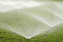 Irrigação da grama com sistema de extinção de incêndios da água fotografia de stock