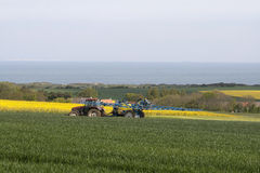 Irrigate crops. A tractor irrigating crops. Sea in the background royalty free stock image