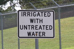 Irrigated with untreated water sign. Black and white sign text irrigated with untreated water and fence in background Royalty Free Stock Photography